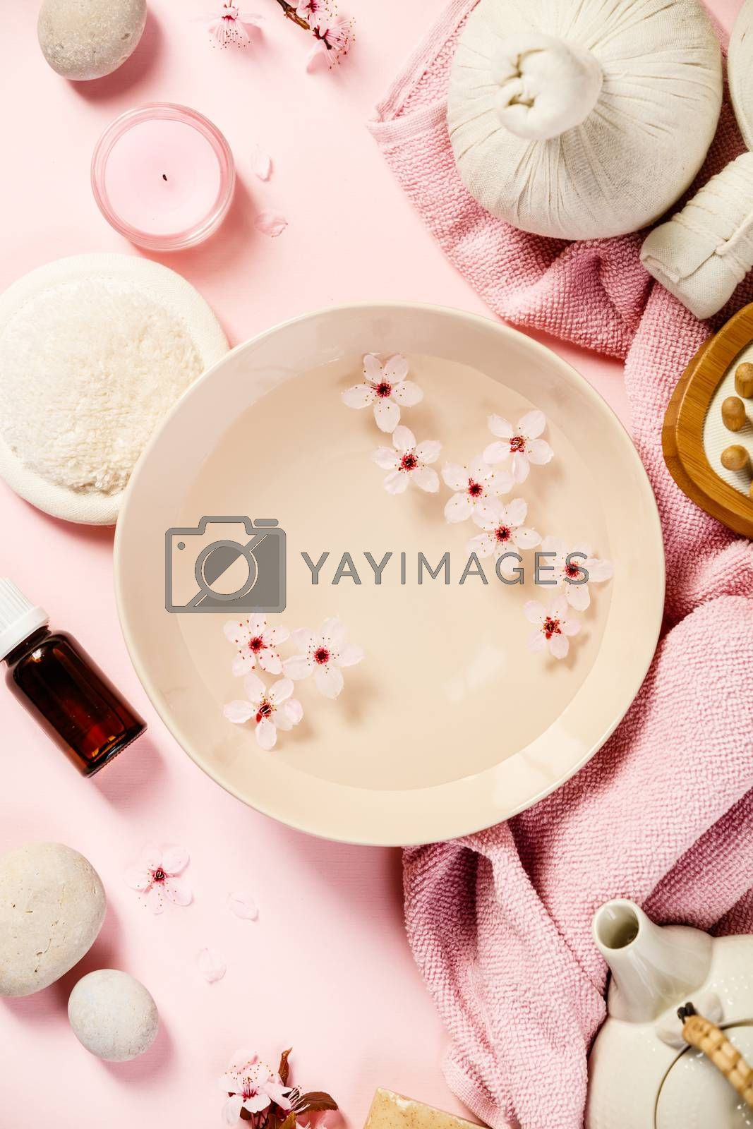 Aromatherapy, beauty, spa background with towel, perfumed flowers water, tea pot, essencial oil and candles on pastel pink background, top view. Relaxation and zen like concept. Flat lay.