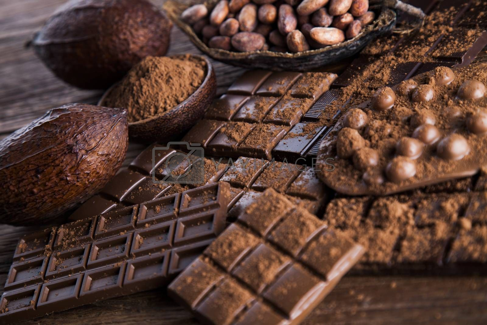Royalty free image of Dark homemade chocolate bars and cocoa pod on wooden  by JanPietruszka