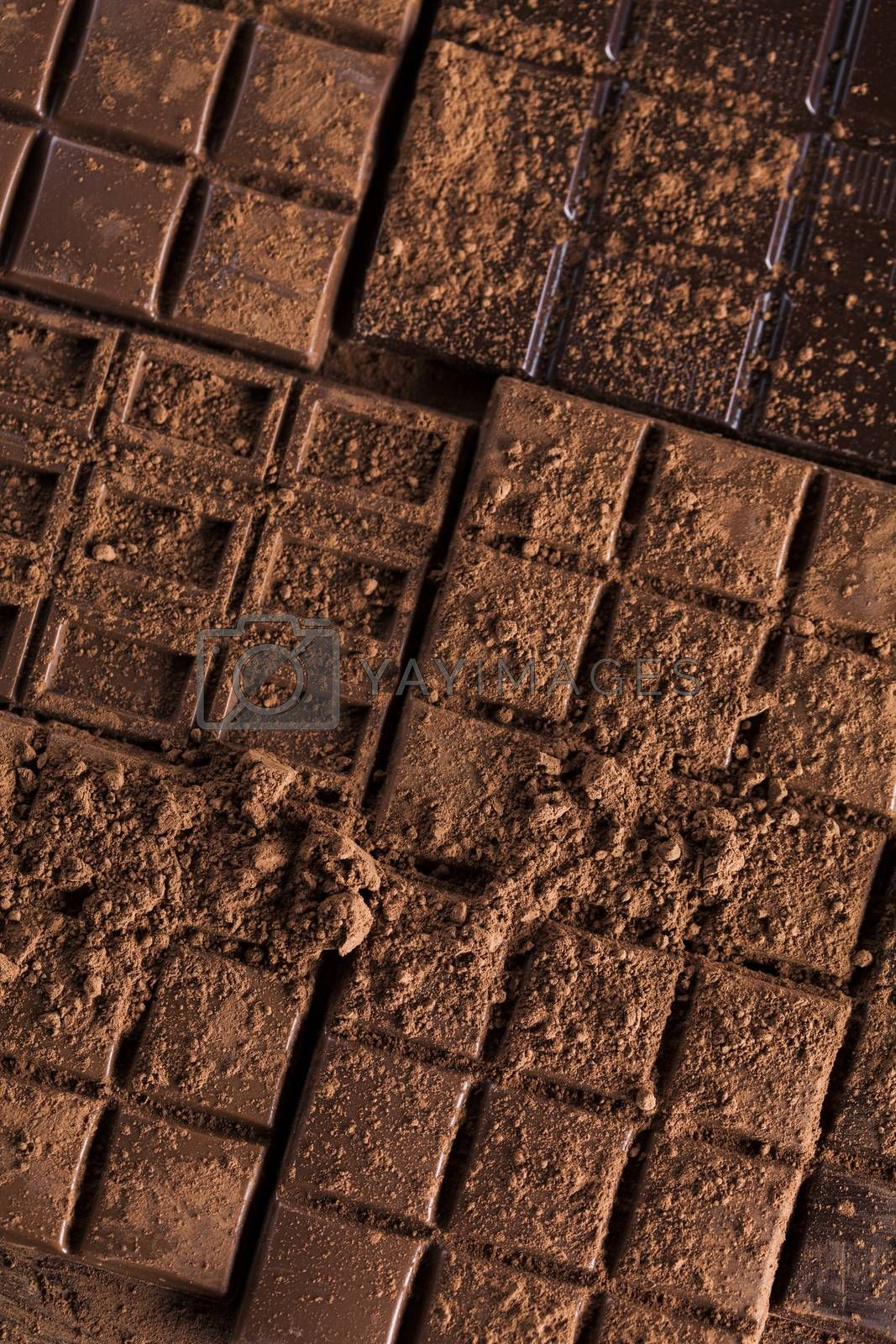 Royalty free image of Dark and milk chocolate bar on a wooden table  by JanPietruszka