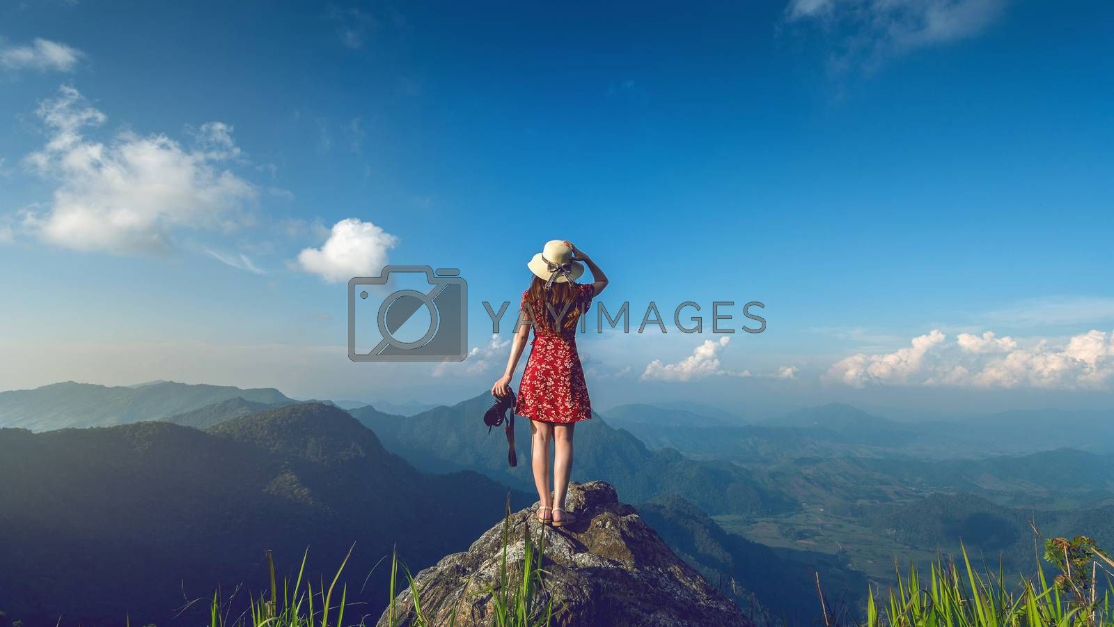 Woman hand holding camera and standing on top of the rock in nature. Travel concept. Vintage tone.