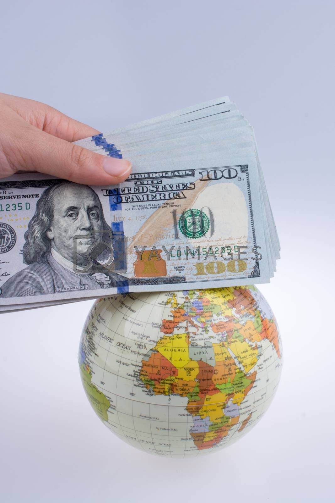Human hand holding American dollar banknotes by the side of a model globe on white background