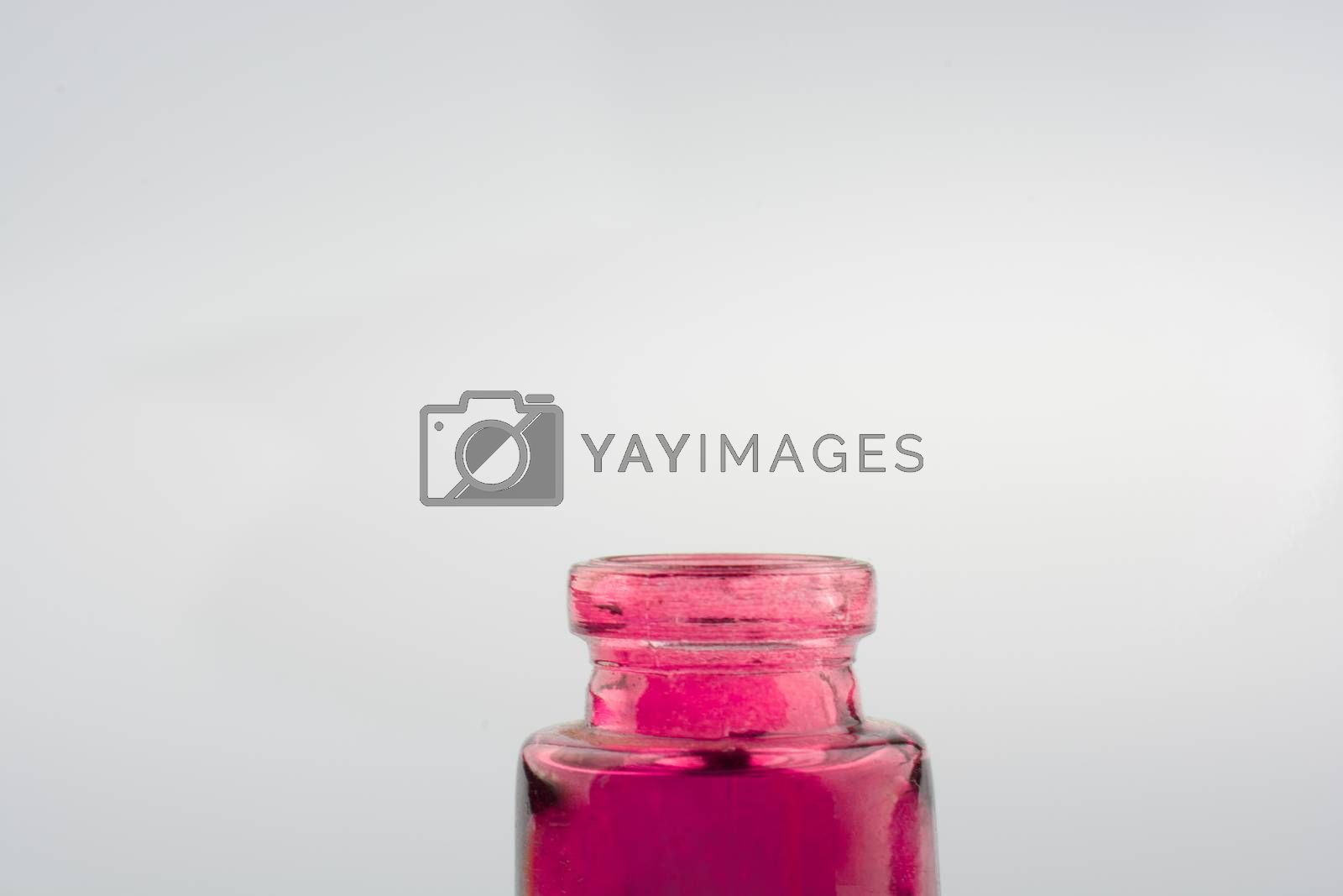 Little colorful empty  glass bottle on a white background
