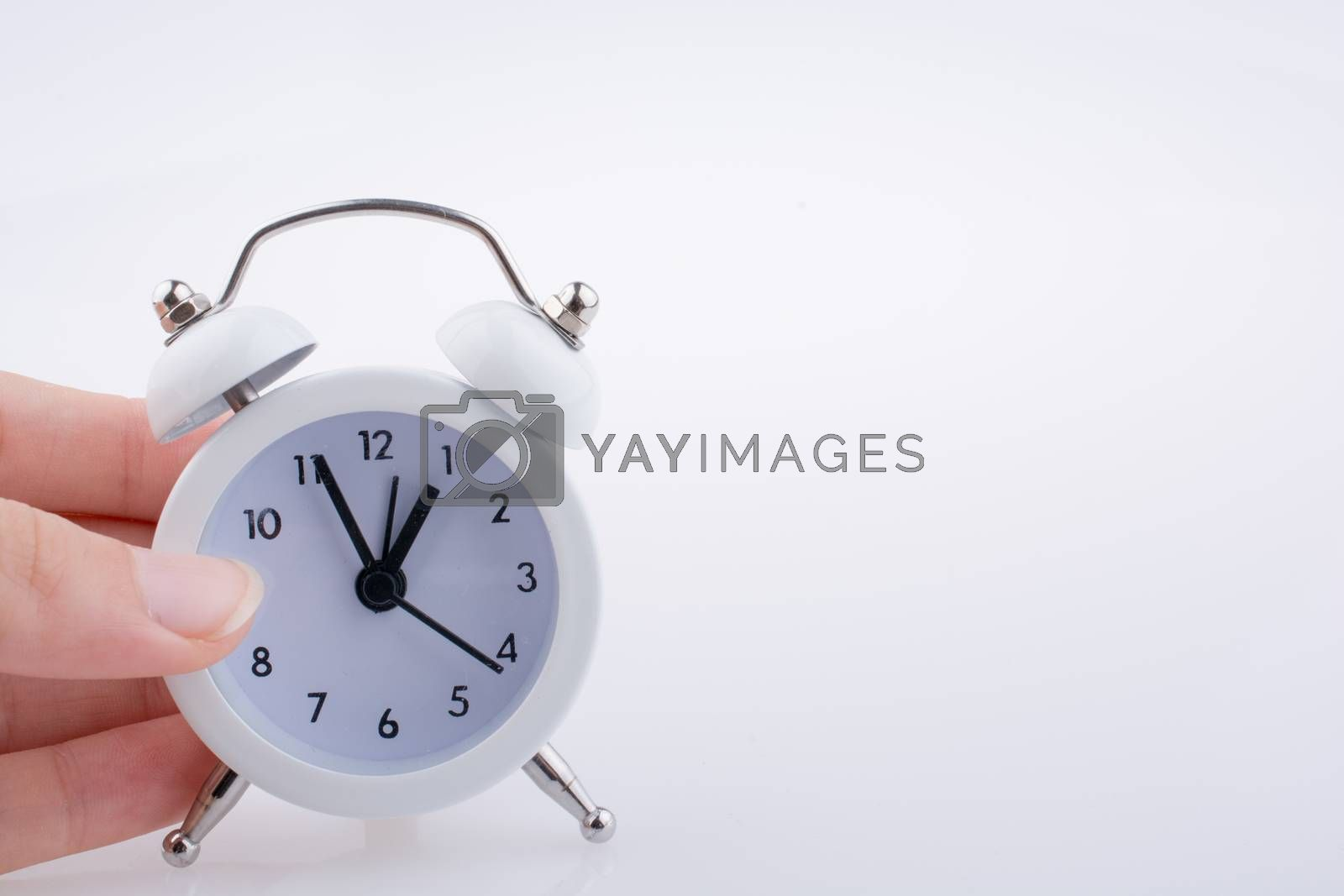 Child  holding an alarm clock  k on white background