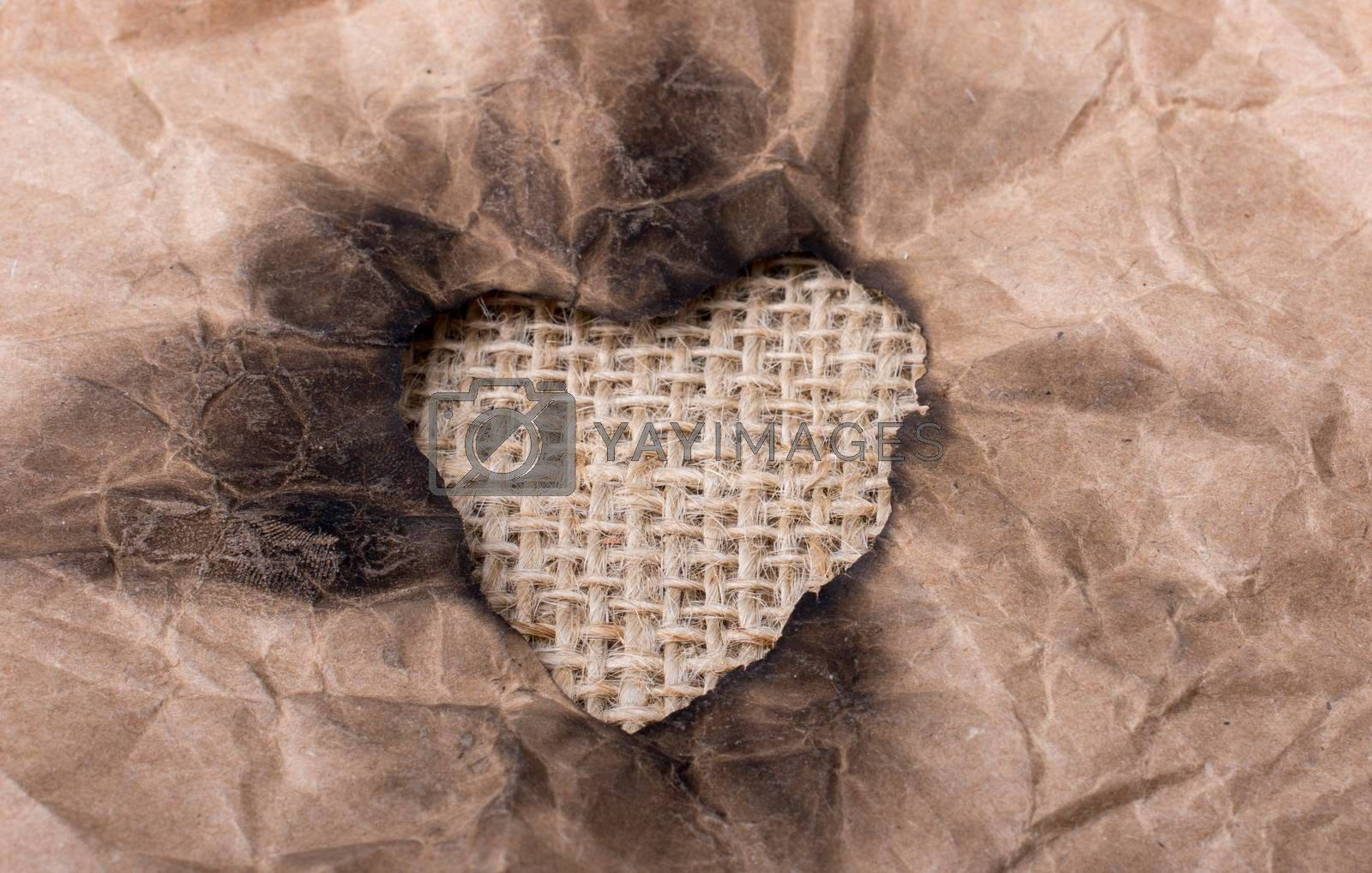 Heart shaped burnt out of a brown paper