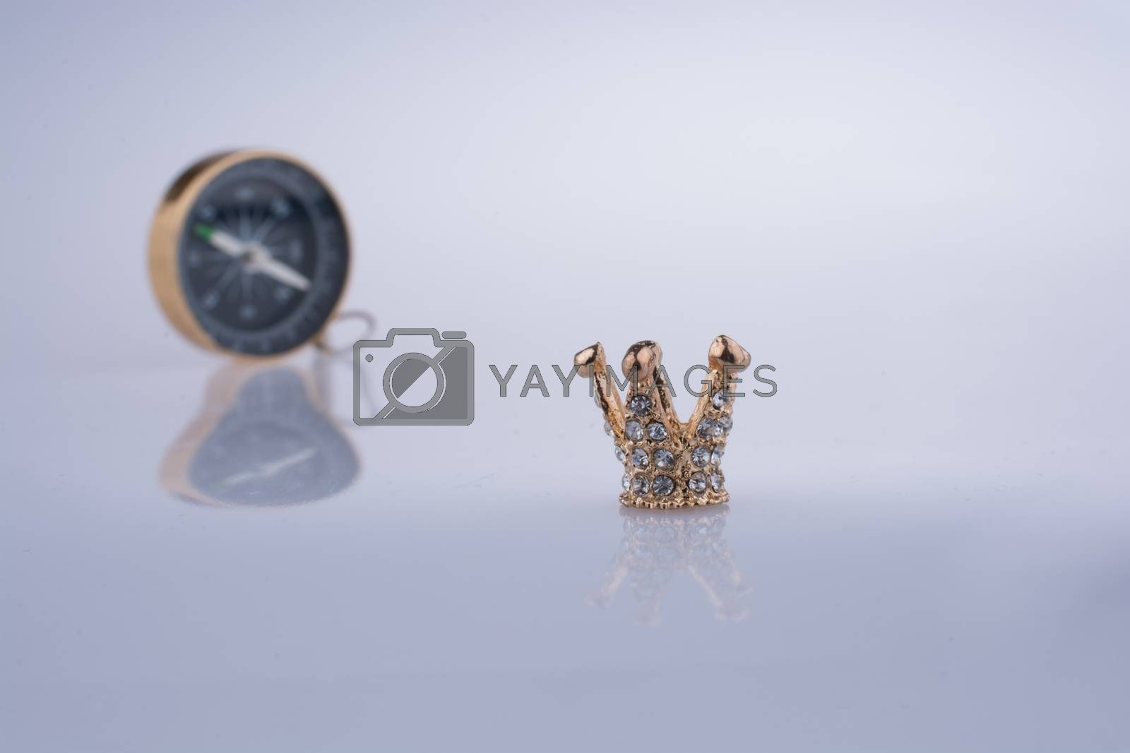 Compass and Golden color crown model with pearls on white background