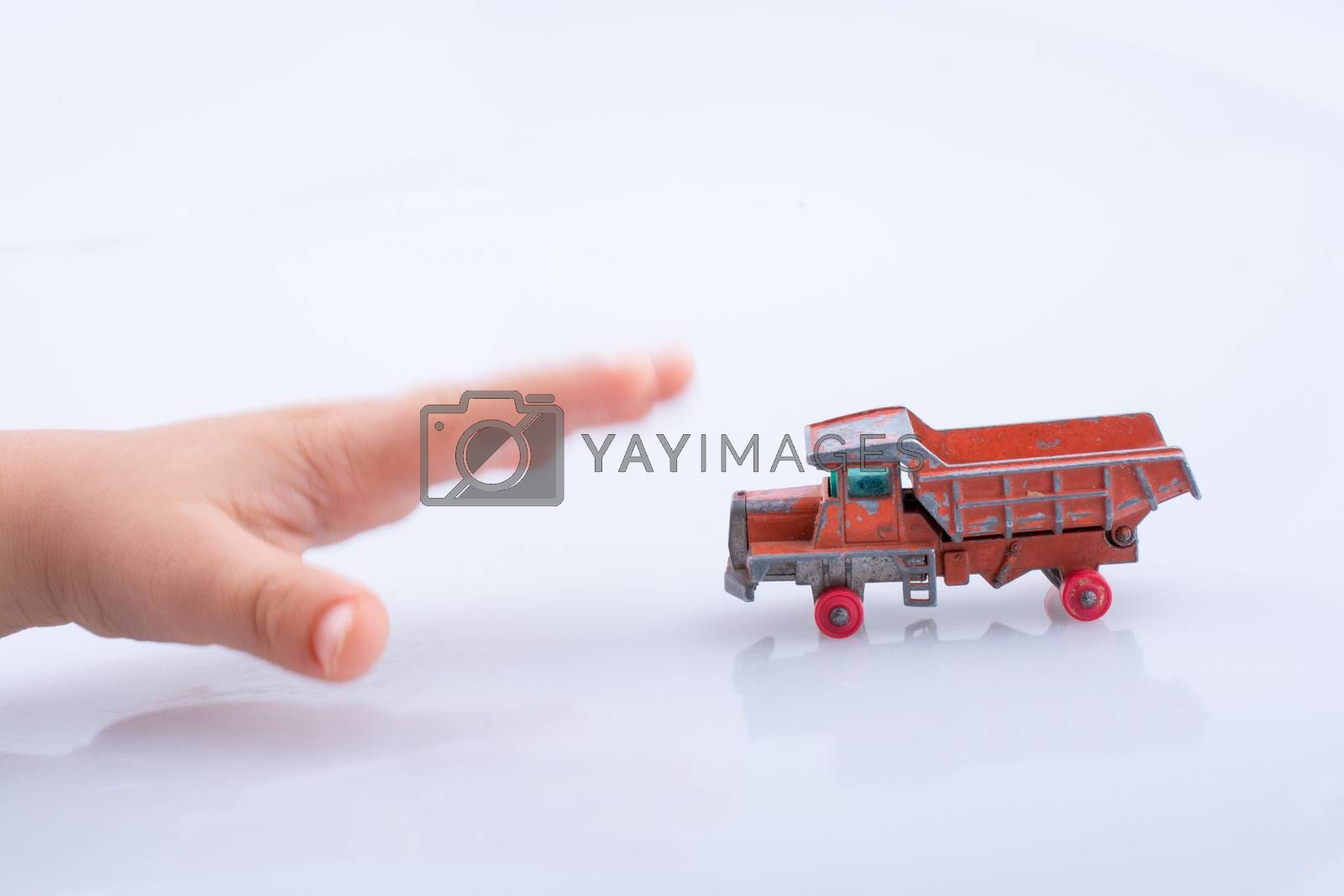 Baby hand is about to grab a red  toy truck on white background