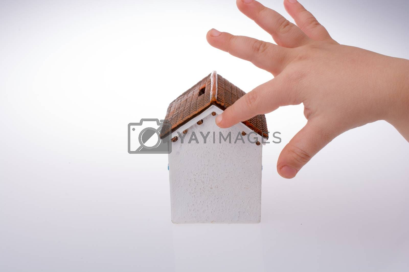 Little model house and  a hand  on a light white color background