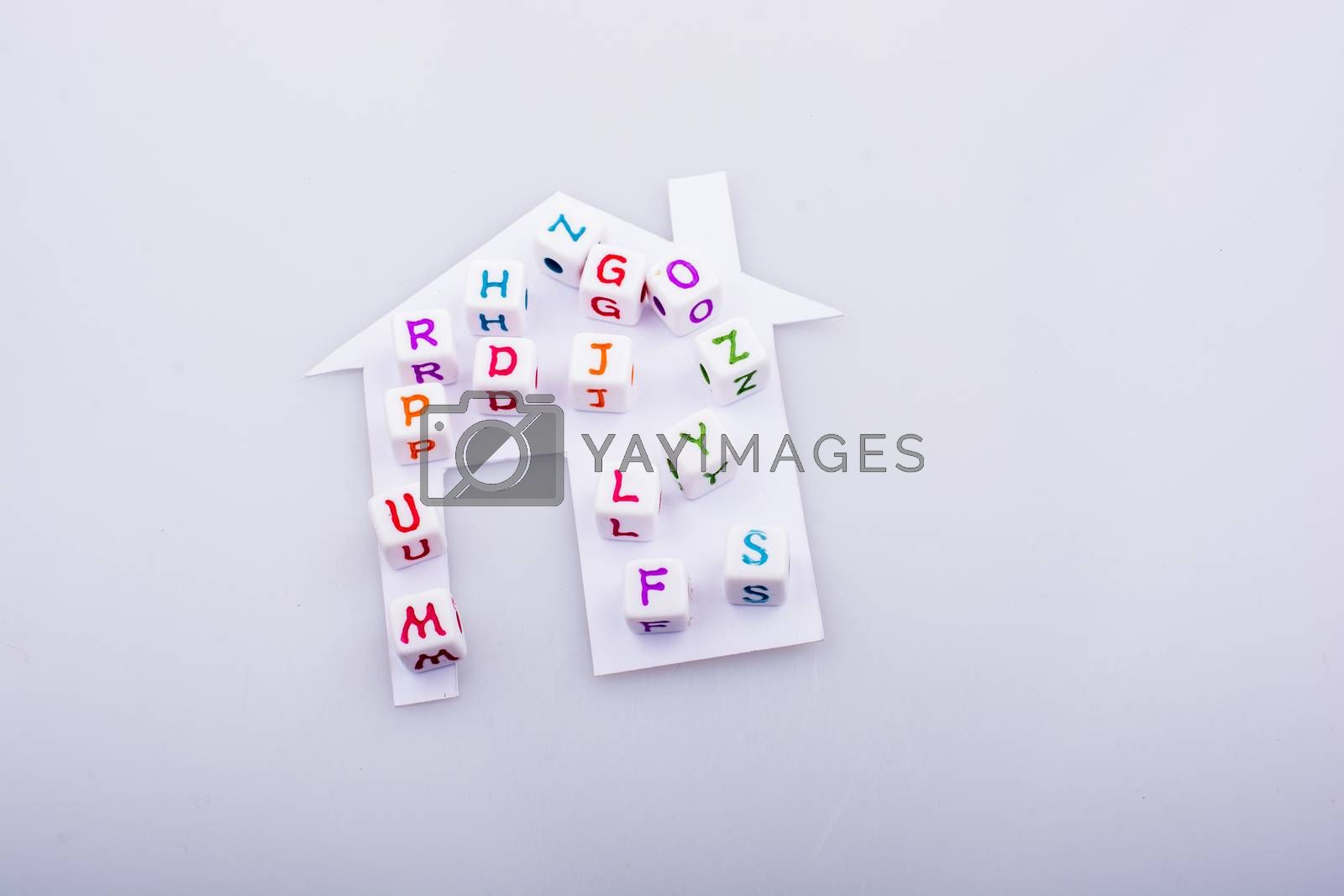 Letter cubes on house shape cut out of paper