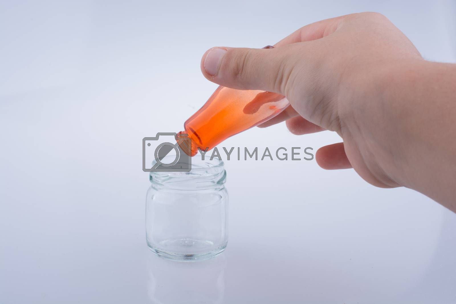 Little colorful  bottle over a jar on a white background