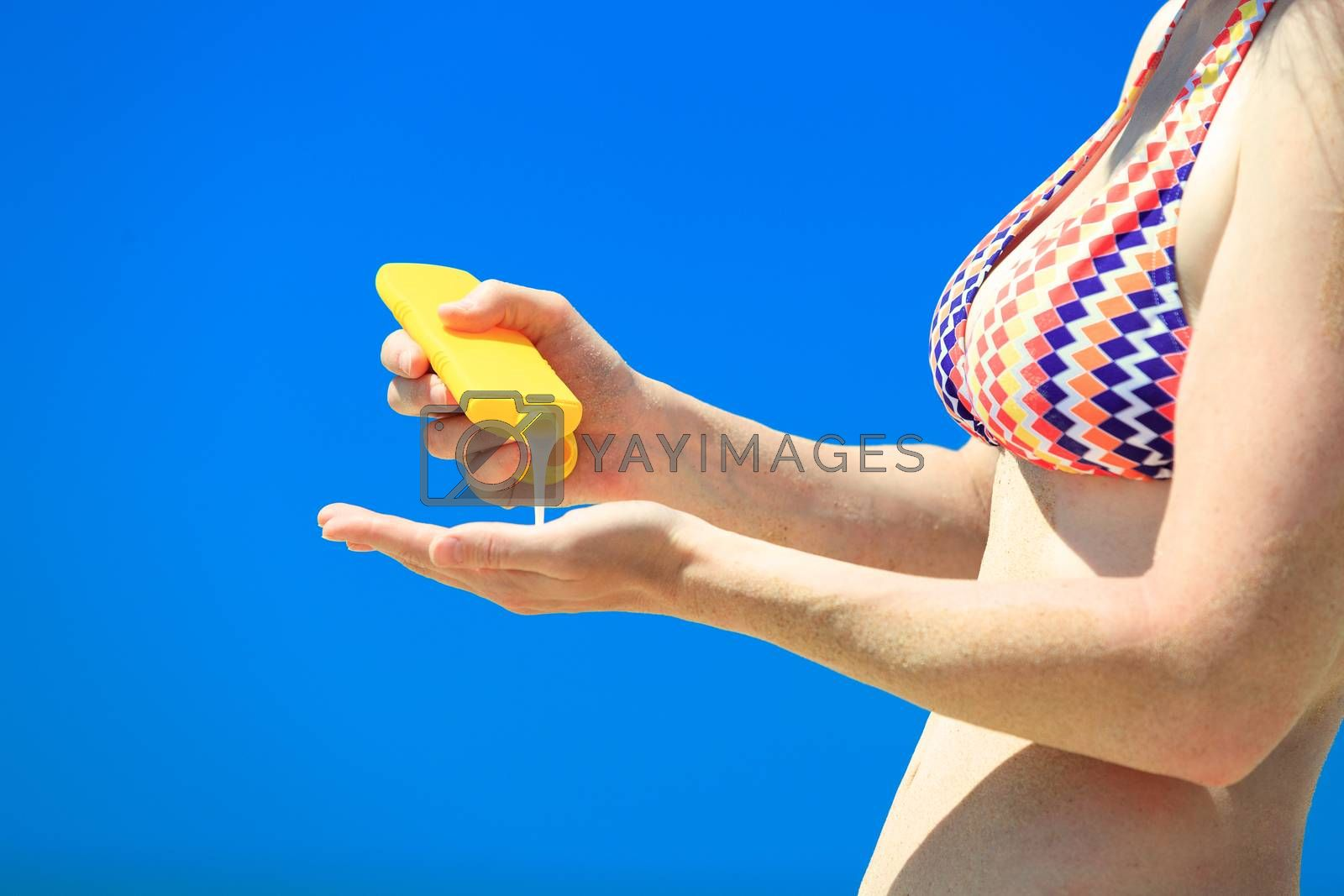Closeup shot of female hands with a yellow bottle of sun protection cream on the blue sky background. Skin care and protection concept.