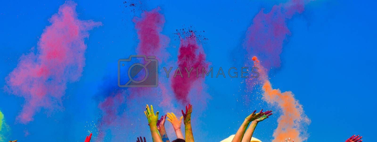 At the color Holi festival, hands in the air, blue sky behind