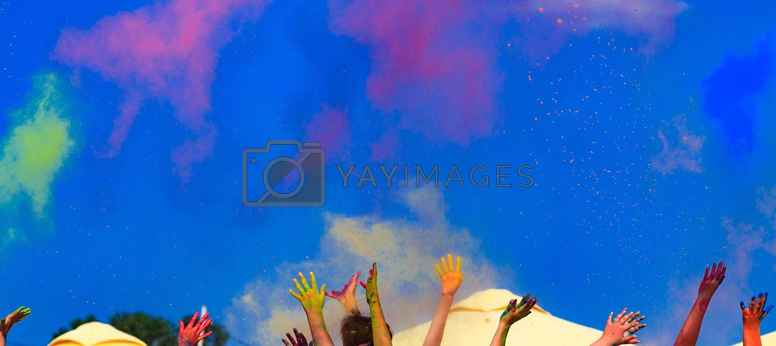 At the color Holi festival, hands in the air, blue sky behind by Nobilior