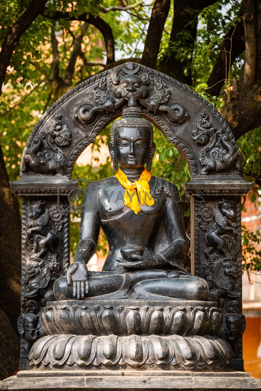 Statue of Buddha wearing an orange khata (scarf) in Patan, Nepal