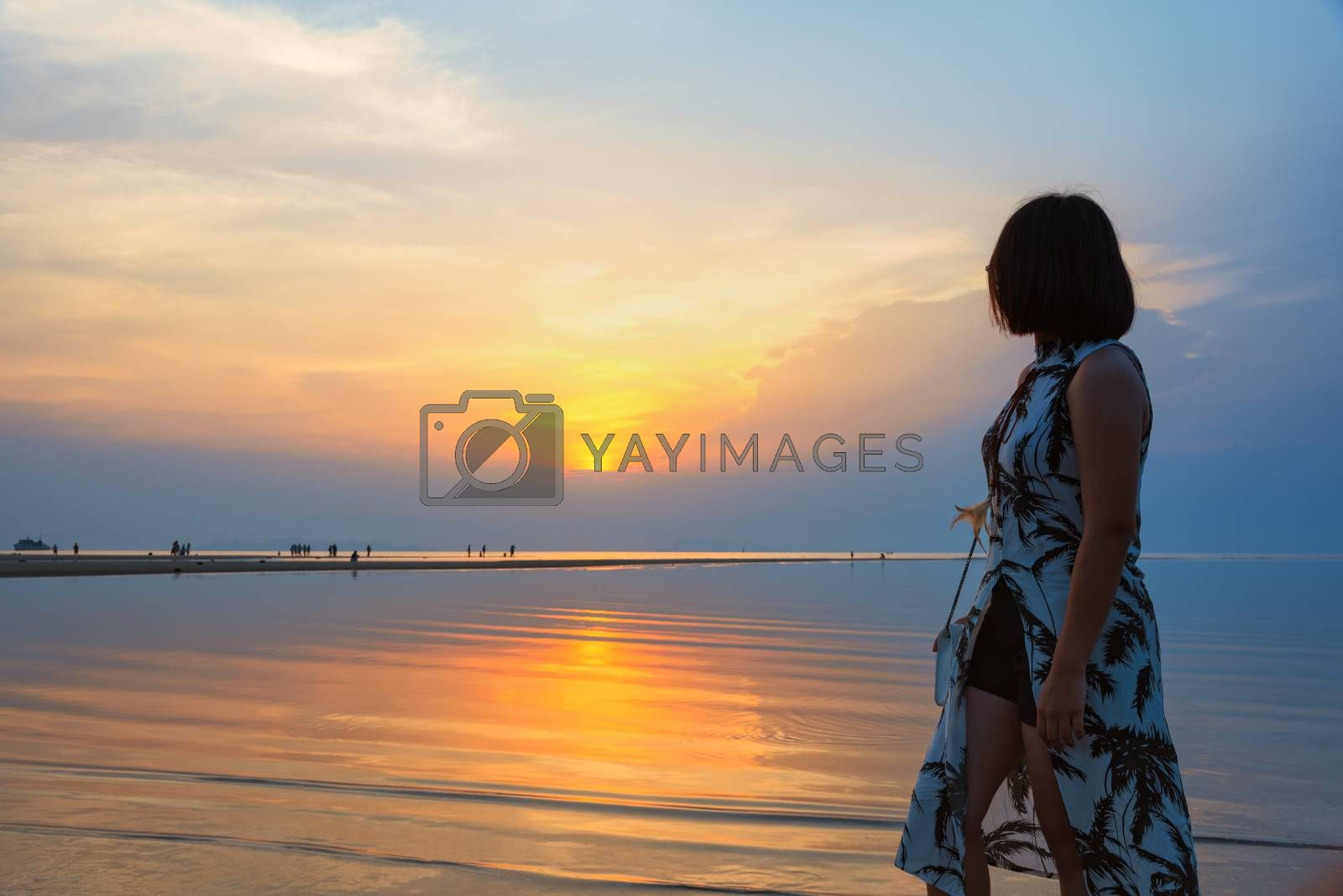 Young woman are standing watching the beautiful natural landscape, colorful of the sky and the sea during a sunset on the beach at Nathon Sunset Viewpoint in Ko Samui island, Surat Thani, Thailand