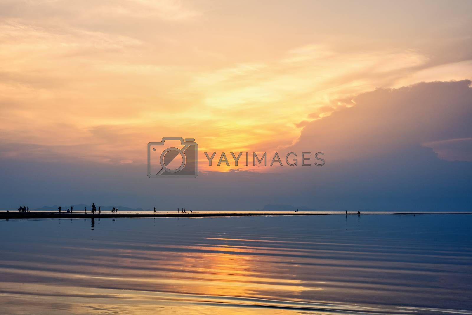 Silhouette of people relaxing on the beach watching the beautiful natural landscape colorful of the sky and the sea during a sunset at Nathon Sunset Viewpoint in Ko Samui island, Surat Thani, Thailand