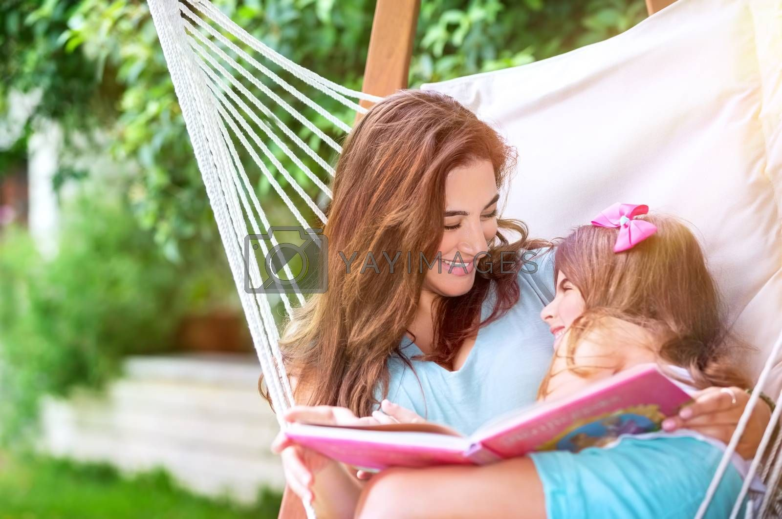 Cheerful mother with baby daughter having fun outdoors, relaxing in hammock and reading funny story, happy family spending time in countryside