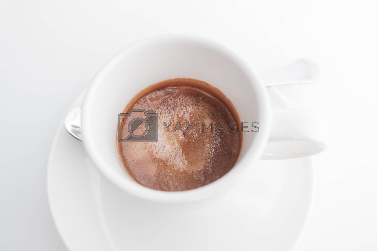 Espresso coffee in white cup on white table. High key style shot.