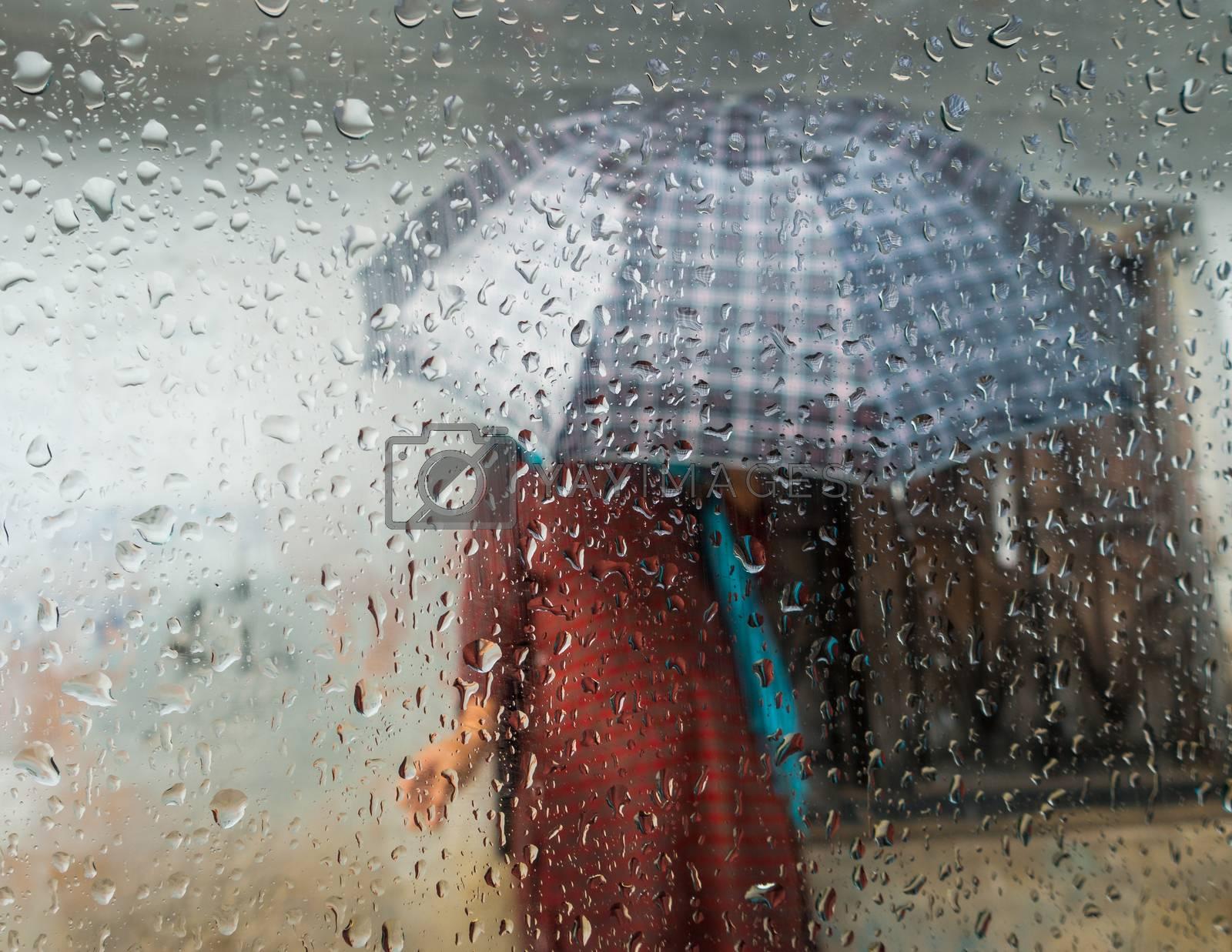 Monsoon season in Kathmandu, Nepal. Woman holding an umbrella seen through a window. Focus on droplets on glass.
