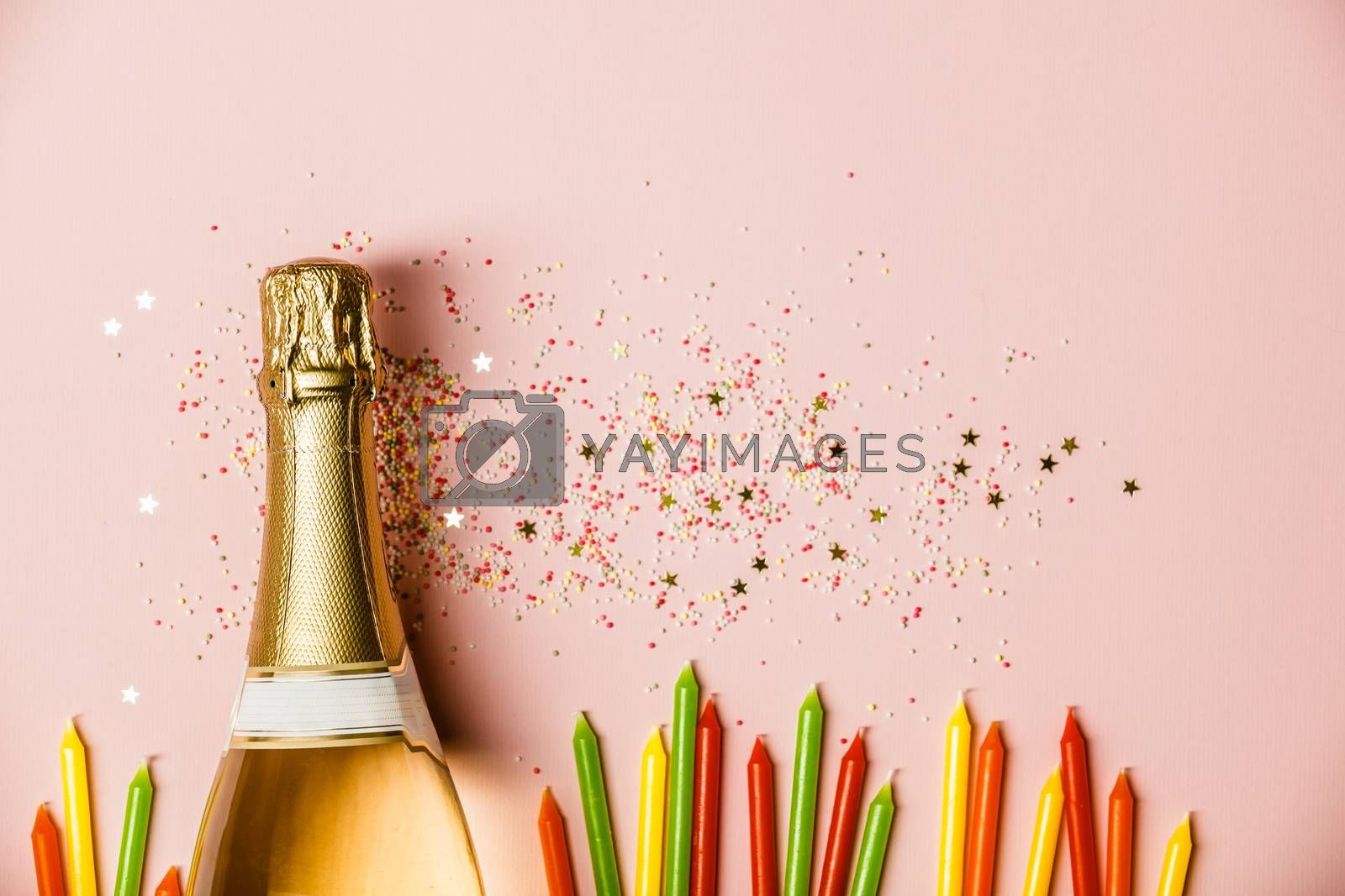 Flat lay of Celebration. Champagne bottle with ice cream sprinkles, golden star sprinkles and birthday candles on pink background. Top view
