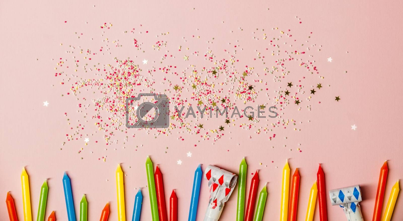 Flat lay of Birthday Celebration. Candles, whistles and sprinkles on pink background. Festive holiday background. Celebration concept.