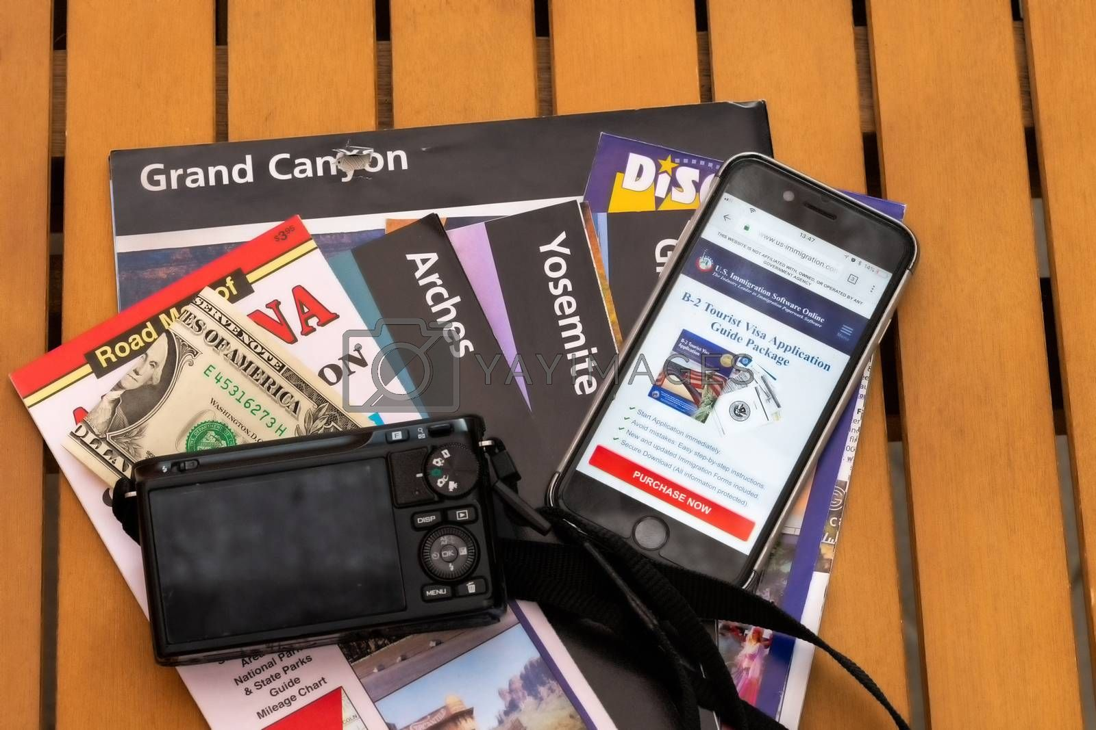 Travel planning accessories, camera, smart phone and travel maps, various USA maps, travel preparation and planning concept to Lake Powell area, mobile phone displaying Visa application
