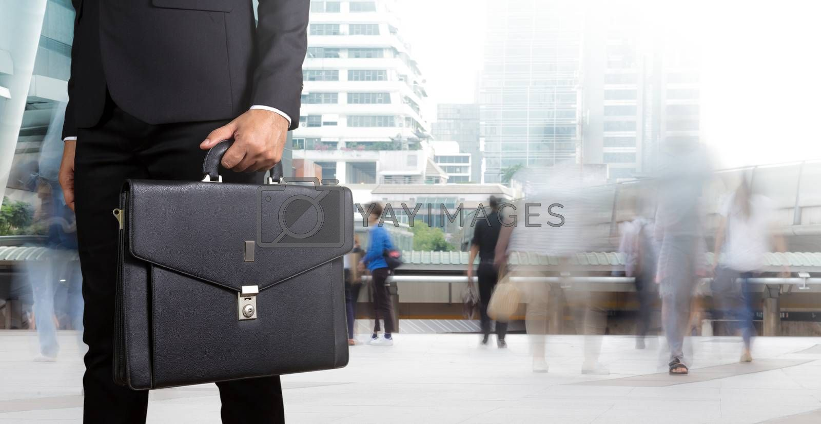 Businessman holding a briefcase with people walking in motion blur in the city background
