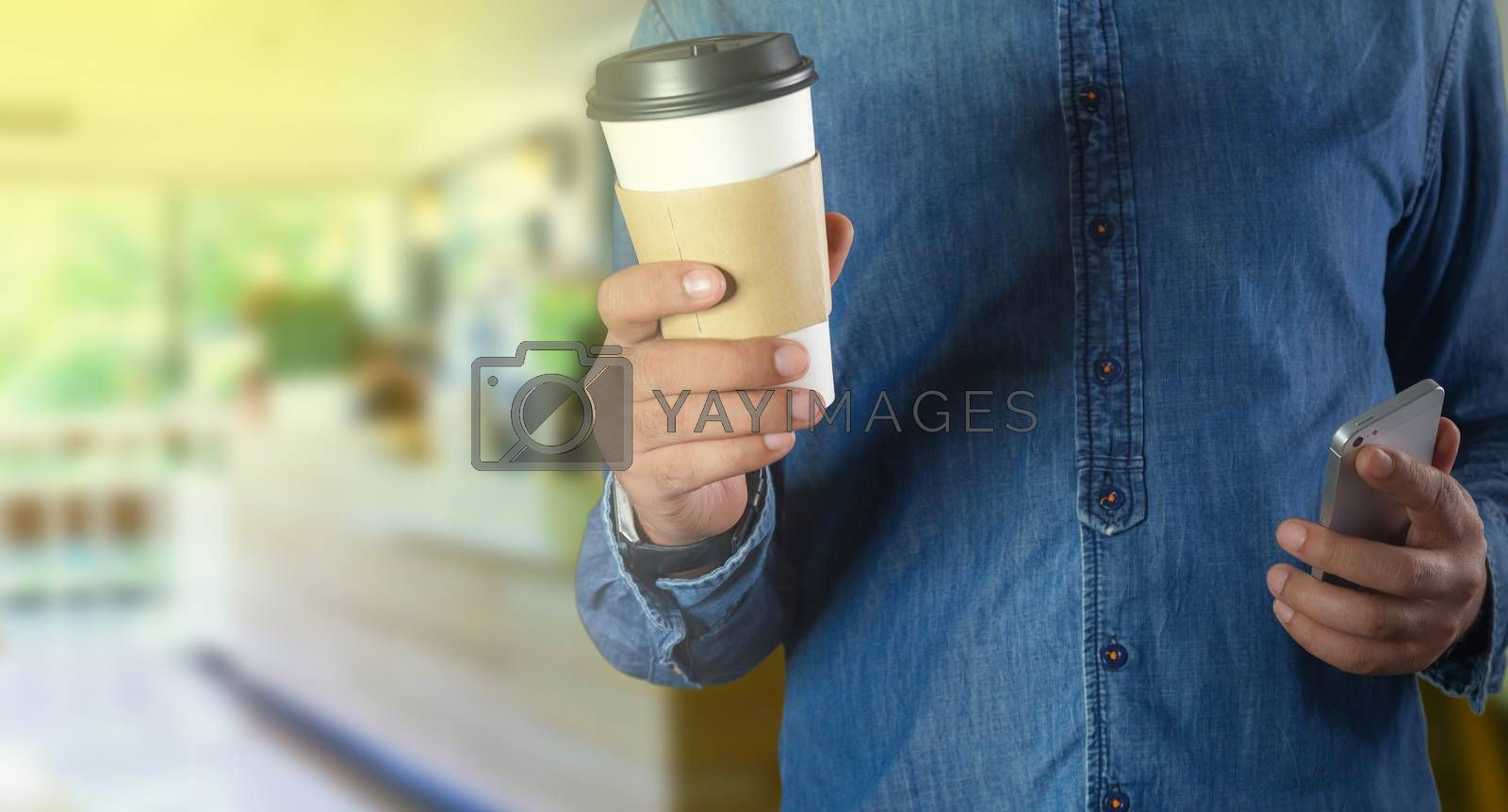 A young man holding a coffee in a coffee shop with phone
