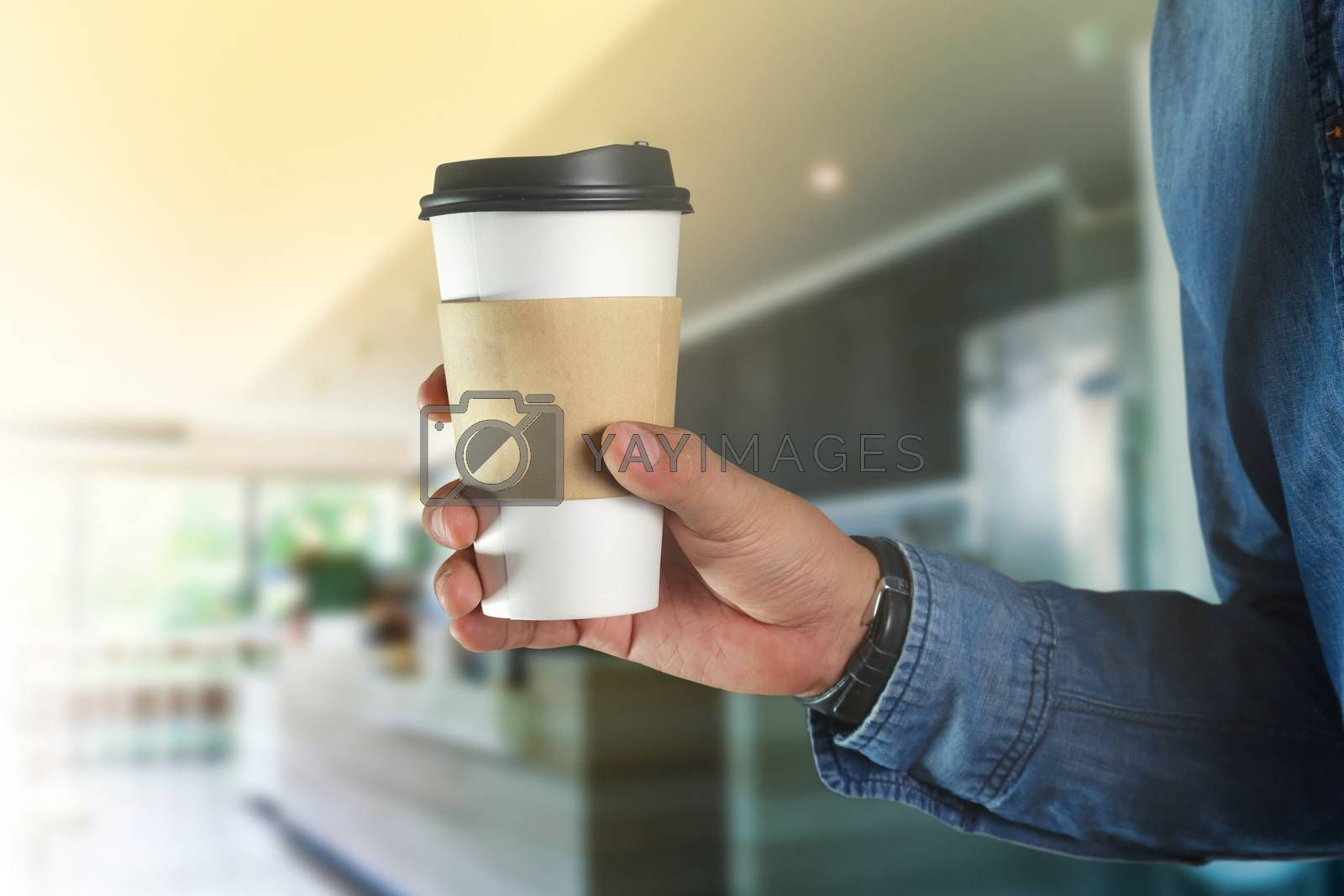 A young man holding a coffee