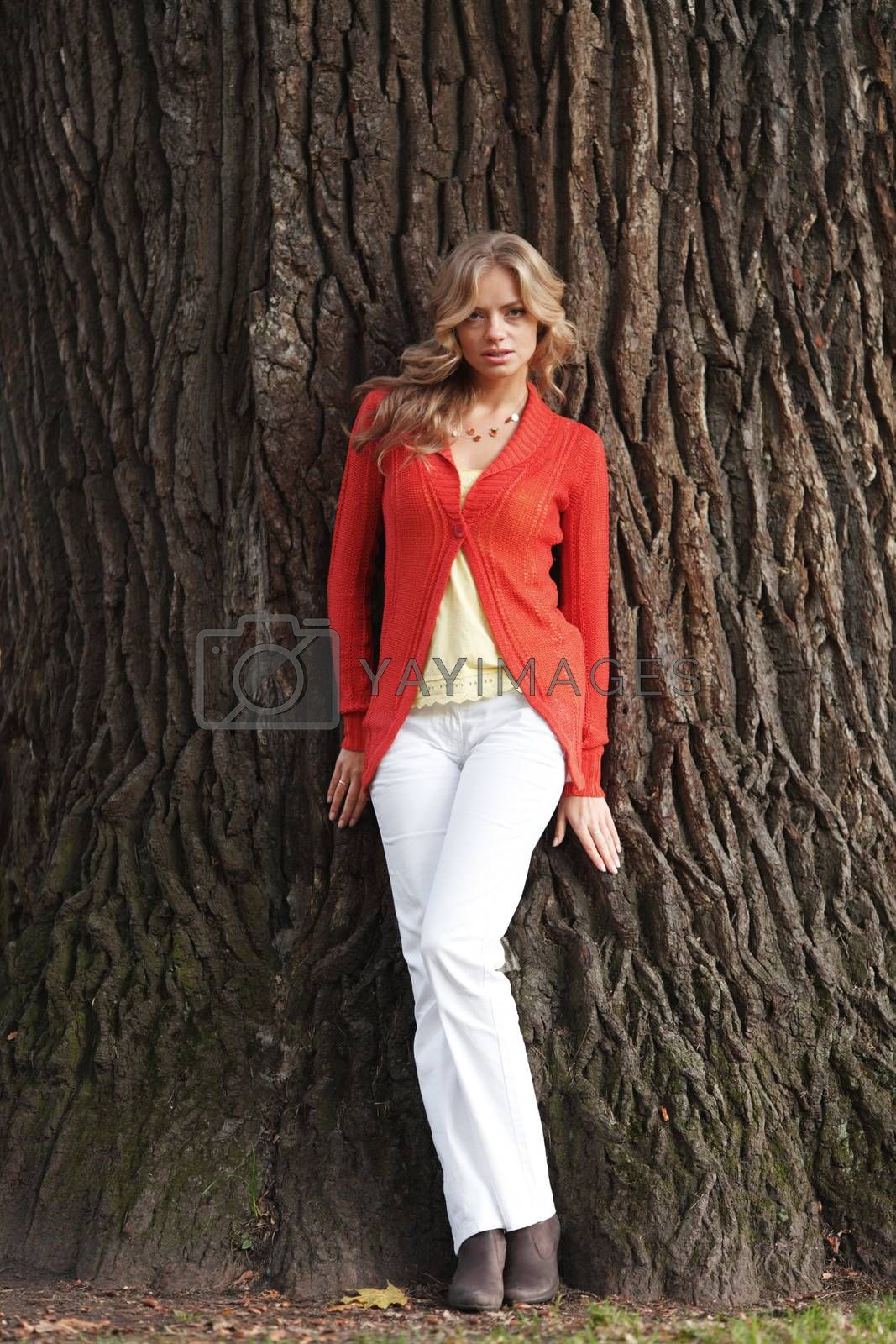 Young fashionable woman posing on tree trunk background