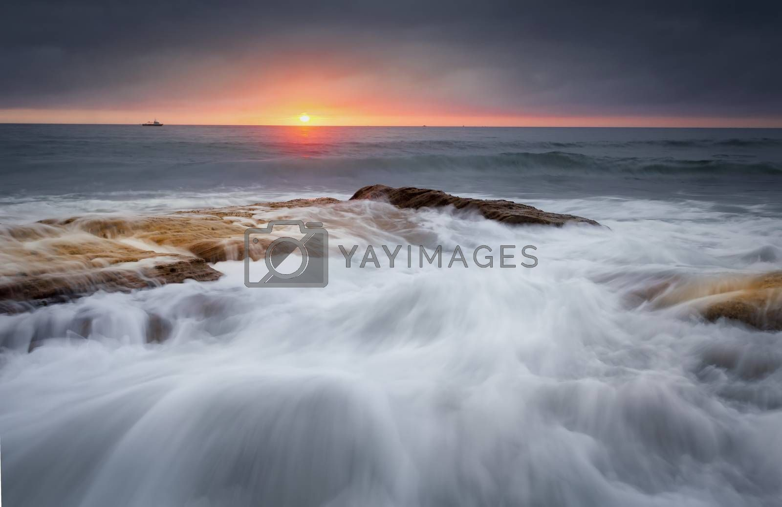 Waves crash over rocks and flow in a myriad of patterns that resemble an artists brush strokes. A break in the storm clouds allowed  a brief viewing of the sun as it rose over the horizon.