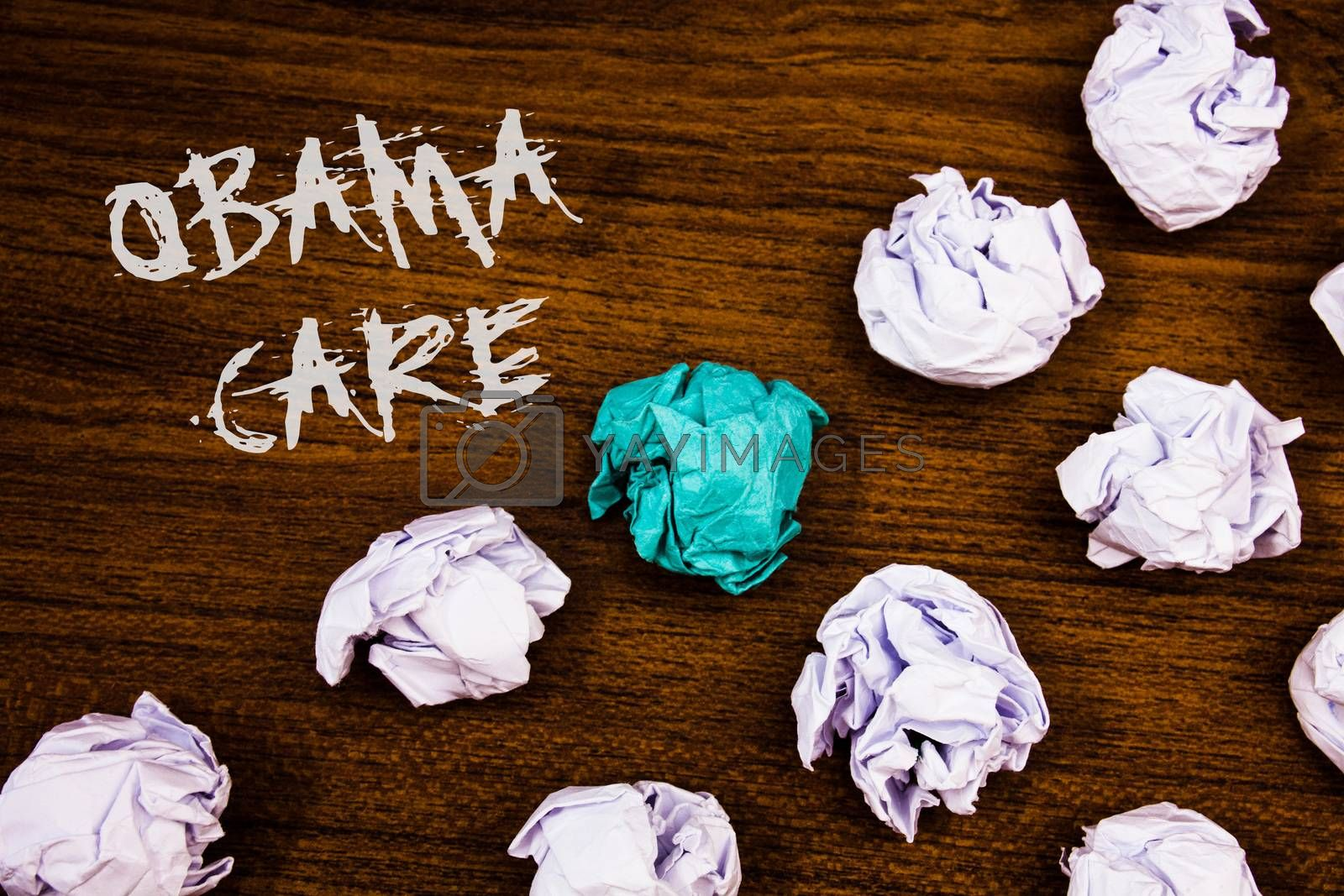 Writing note showing  Obama Care. Business photo showcasing Government Program of Insurance System Patient ProtectionIdeas words wooden background chalk letters several tries crumpled papers