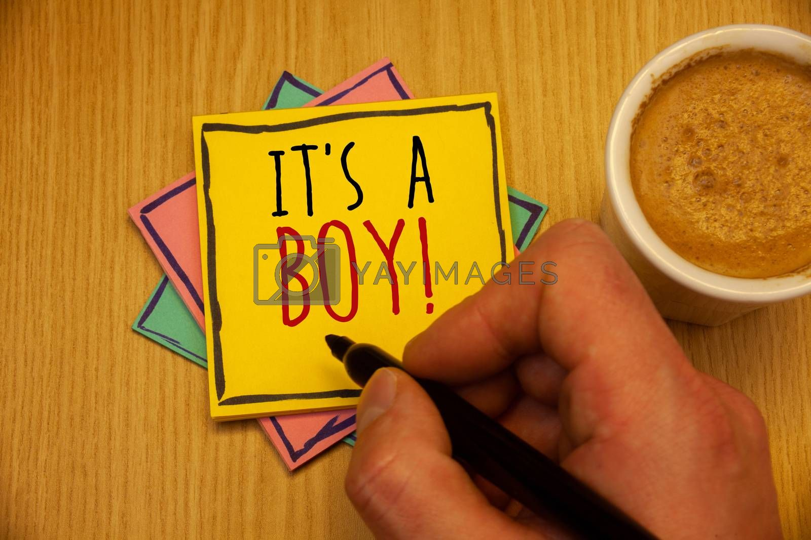 Text sign showing It S A Boy Motivational Call. Conceptual photo Male baby is coming Gender reveal CelebrationMan creating yellow pink blue papers Hand holding black pen cup of coffee