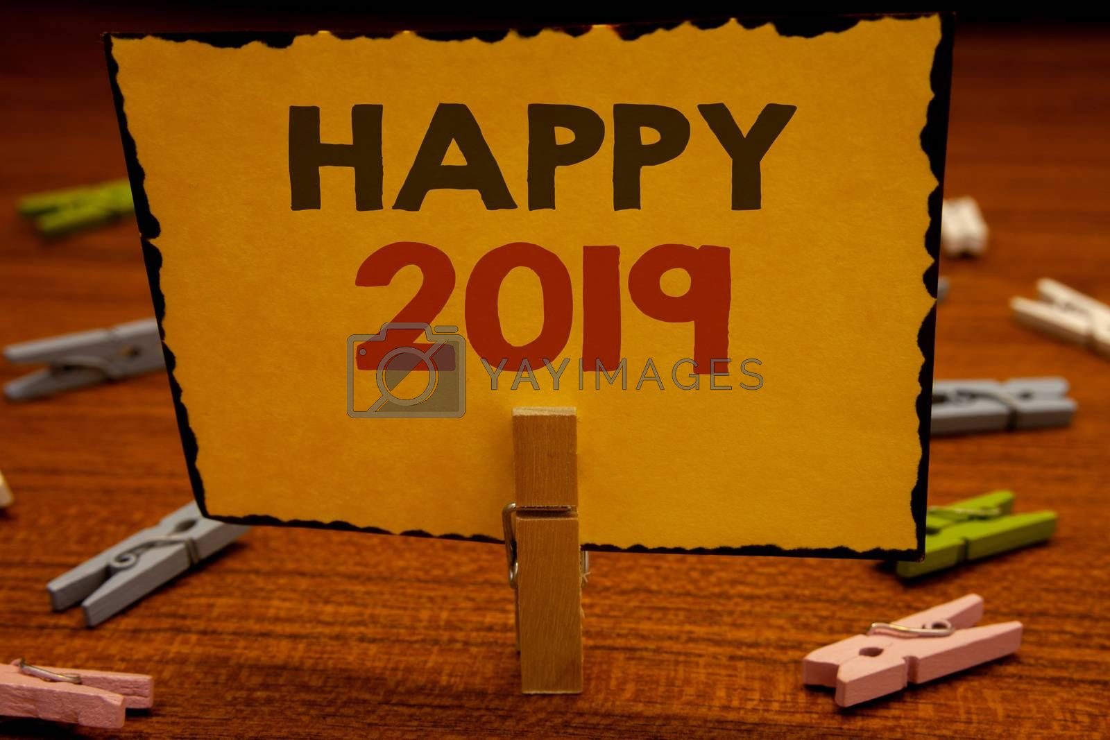 Words writing texts Happy 2019. Business concept for New Year Celebration Cheers Congrats Motivational MessageClothespin hold holding Yellow paper ideas clothespins wooden background