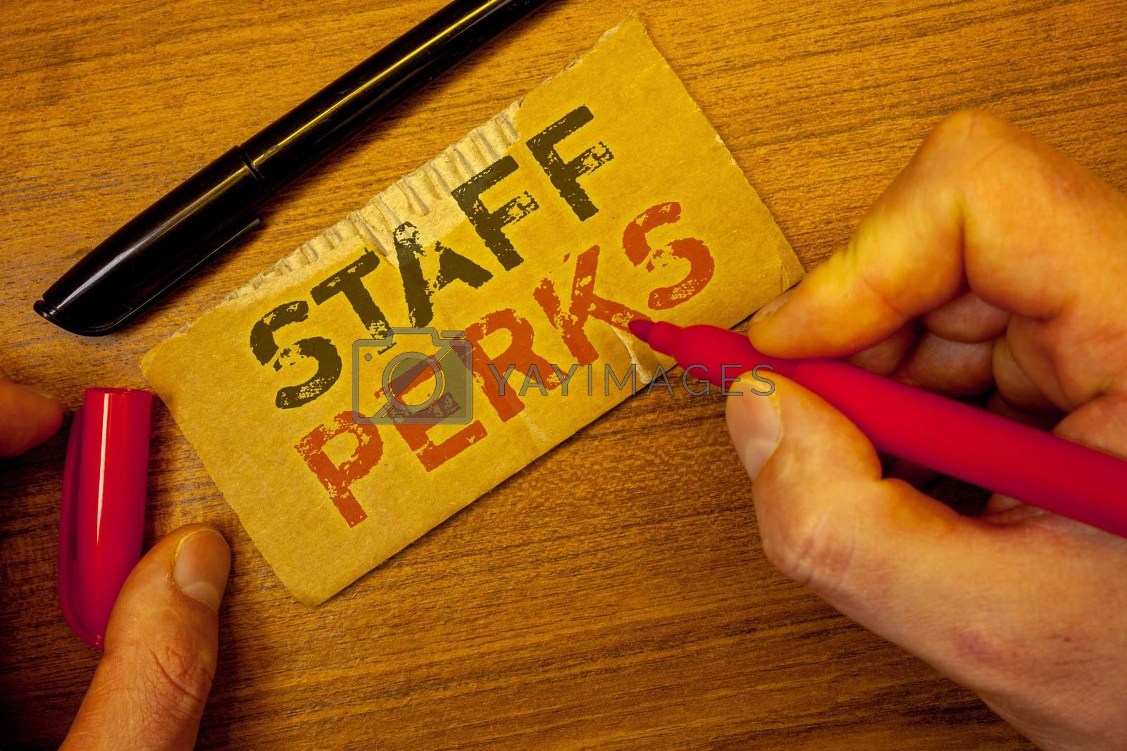 Writing note showing  Staff Perks. Business photo showcasing Workers Benefits Bonuses Compensation Rewards Health InsuranceMan creating on yellow paper Hand holding red black pens wooden table