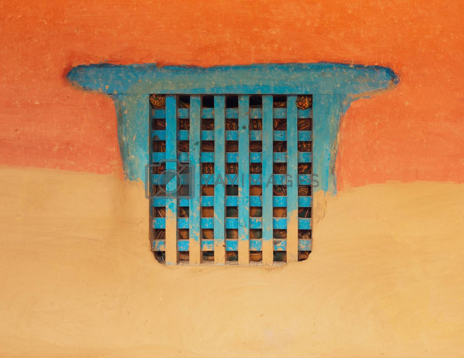 Traditional wooden Nepalese window called Ankhi jhyal. Painted blue on orange and ocher mud wall.