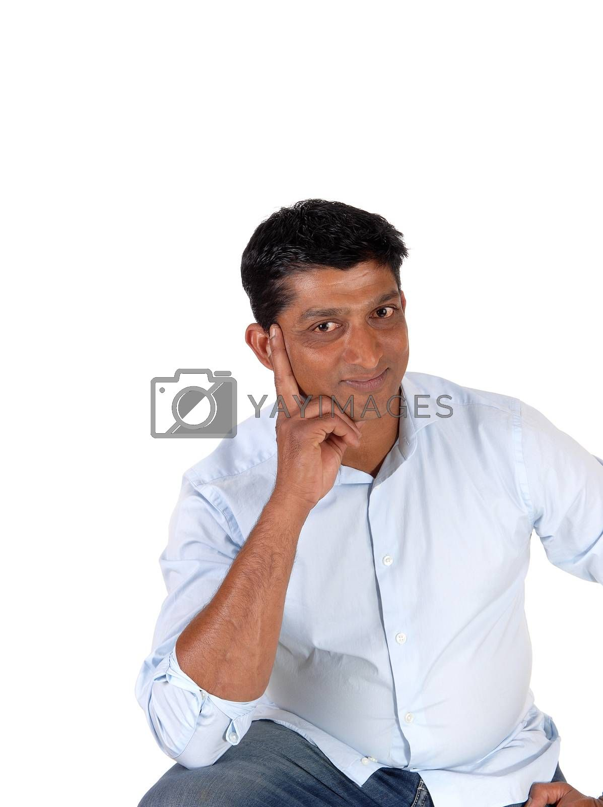 A closeup image of a good looking man in a blue shirt and jeans with one hand on his face, isolated for white background