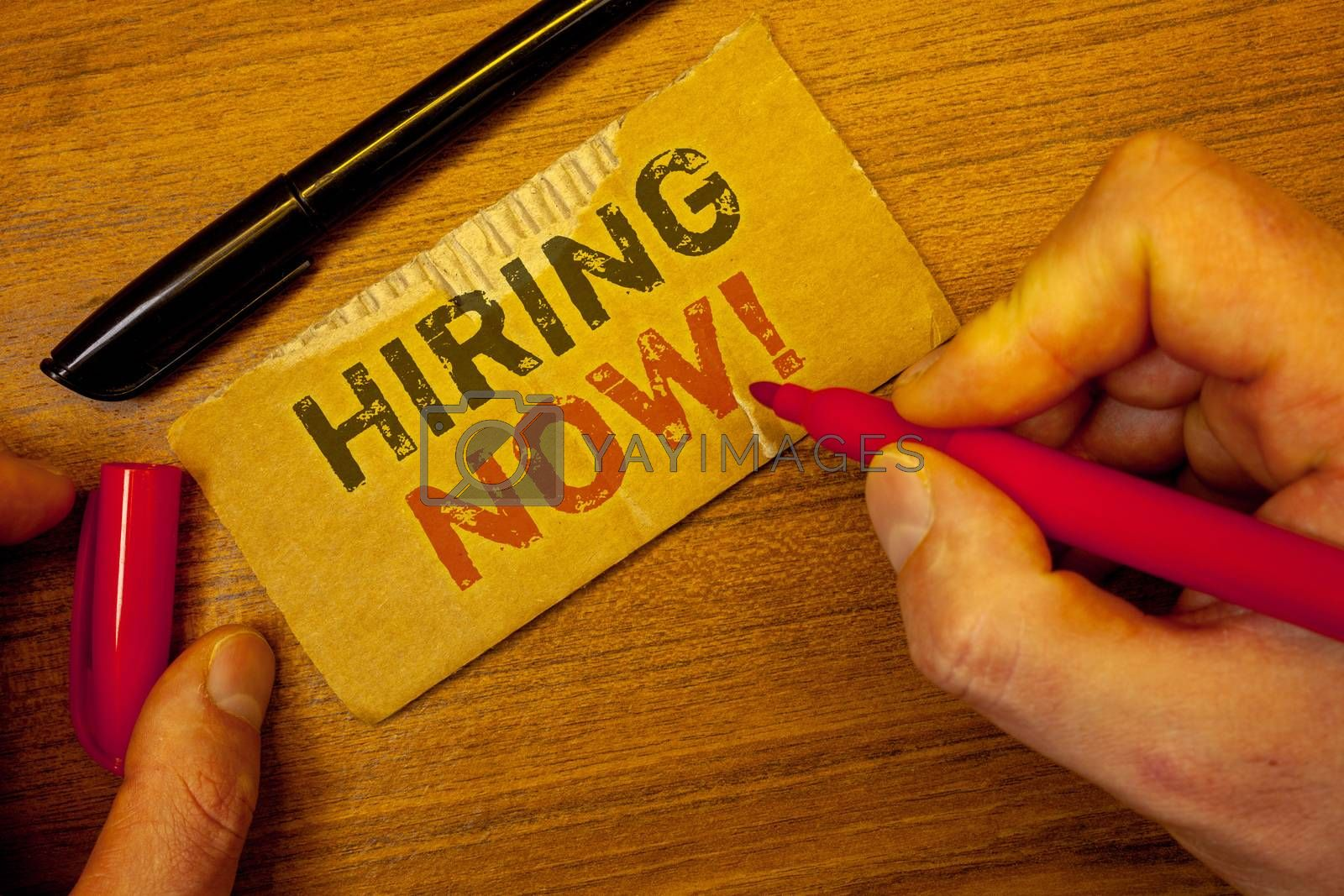 Writing note showing  Hiring Now Motivational Call. Business photo showcasing Workforce Wanted Employees RecruitmentMan creating on yellow paper Hand holding red black pens wooden table