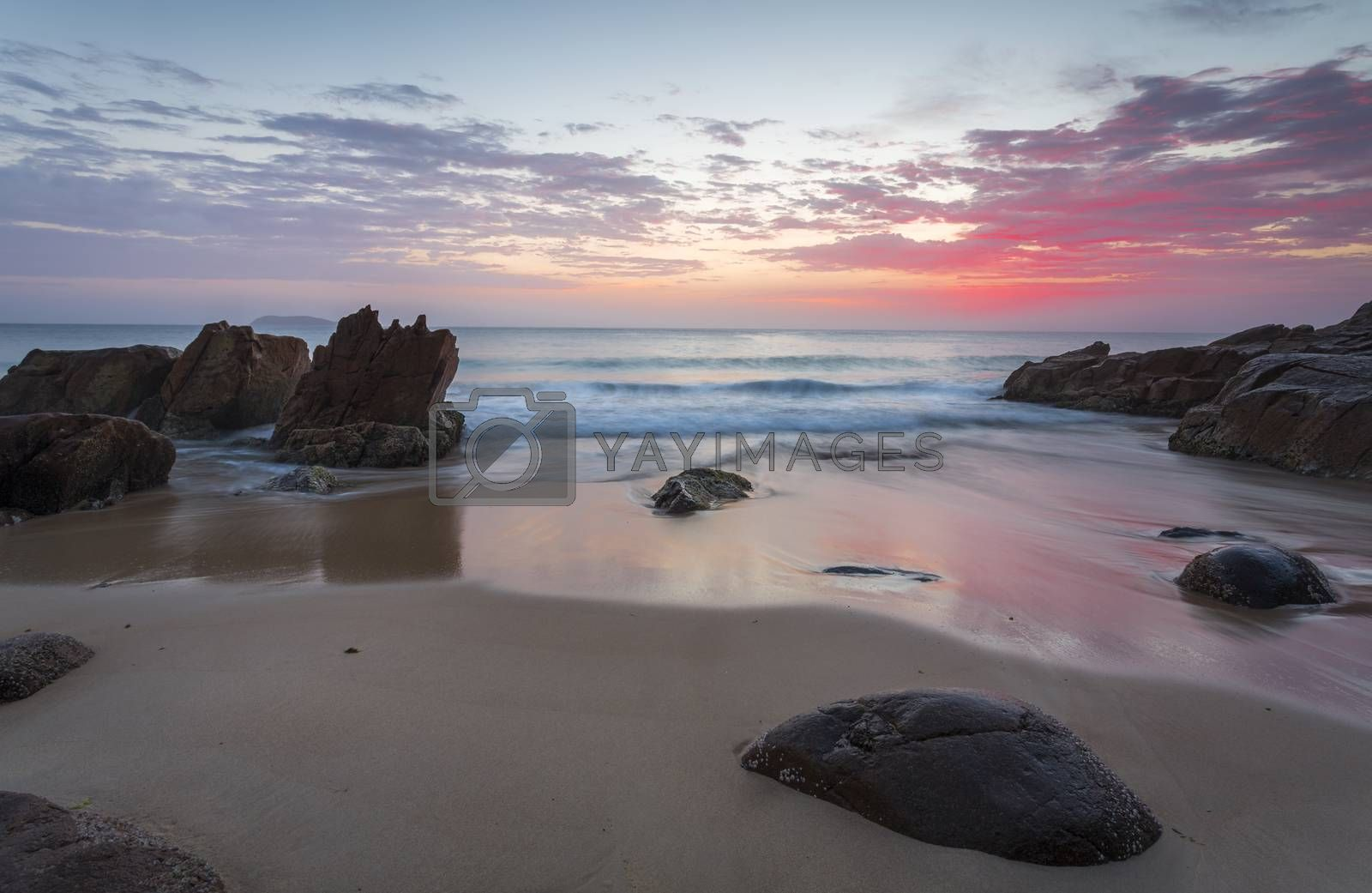 Beautiful colours of the sunrise  and waves flow onto the beach and around rocks.  Location:  Zenith Beach, Port Stephens Australia