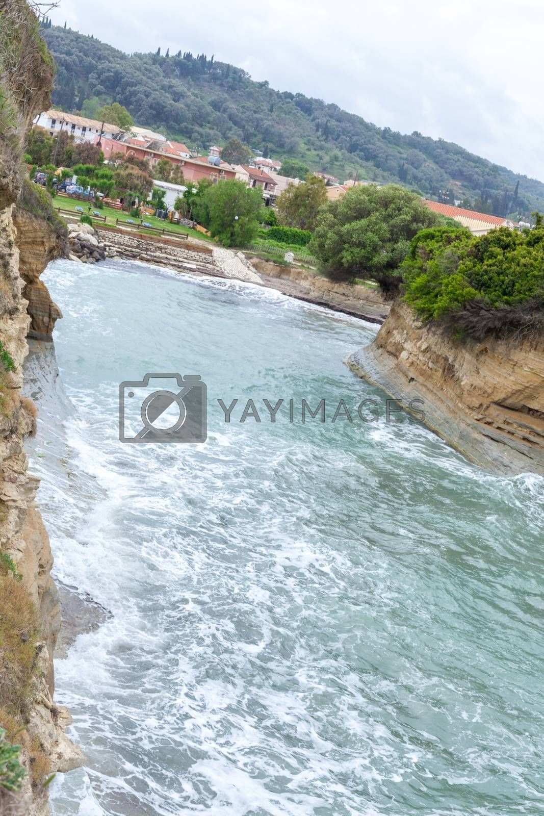 River flowing beside the hill. Water rushing down the stream. Houses built near the riverbed.Scenic view of rural area. Typical scenery of countryside living