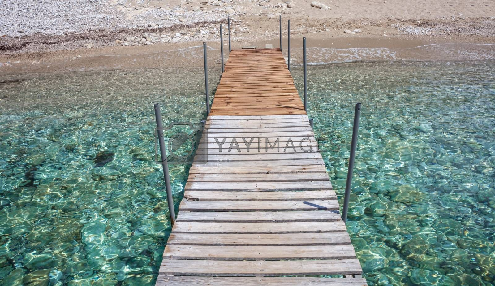 Patterned dock over the water. Wooden post supporting the walk bridge.Crystal clear water glittering under the sun. Scenic view of a travel destination