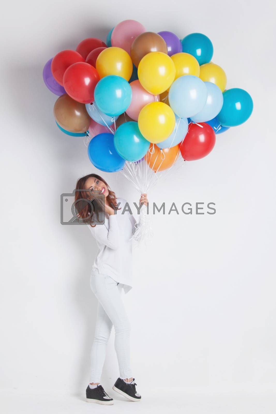 Happy woman with many colorful balloons on white