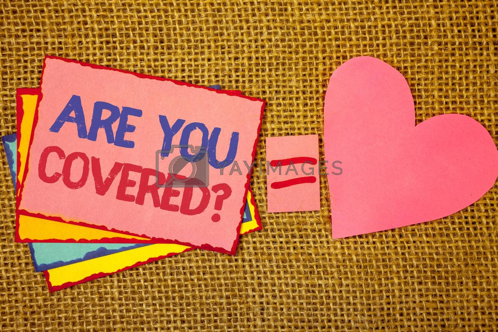 Writing note showing  Are You Covered Question. Business photo showcasing Have a Security and Health Insurance Medical Care Pink yellow blue notes black red letters ideas equal sign heart wicker