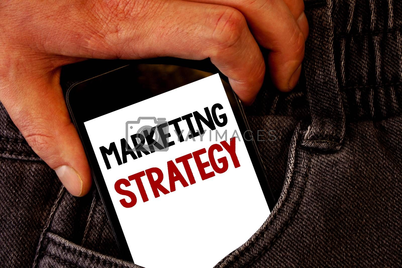 Handwriting text Marketing Strategy. Concept meaning Plan Formula Creativity Research Organization Brown jeans back pocket hand pushing mobile phone with black and red text