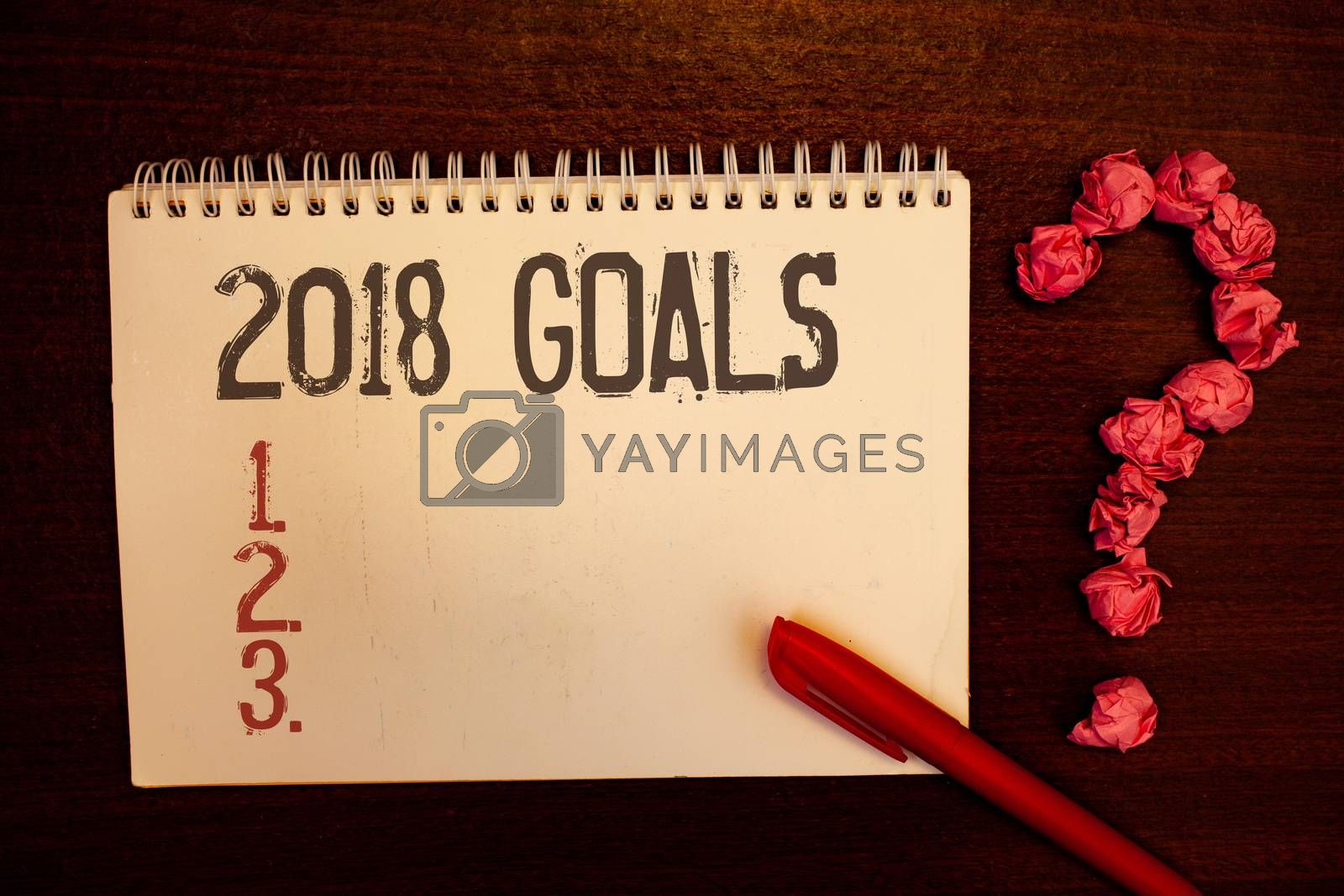 Handwriting text 2018 Goals 1. 2. 3.. Concept meaning Resolution Organize Beginnings Future Plans Reddish paper balls structures question mark red pen notebook browny desk