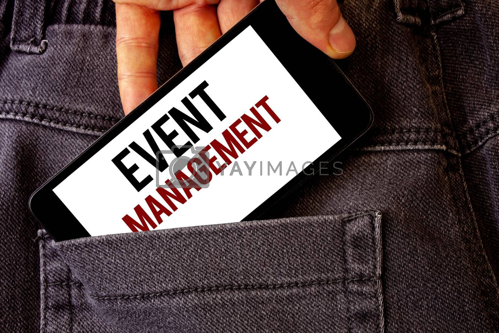 Conceptual hand writing showing Event Management. Business photo showcasing Special Occasion Schedule Organization Arrange Activities Man holding cell phone white screen letters jeans pocket