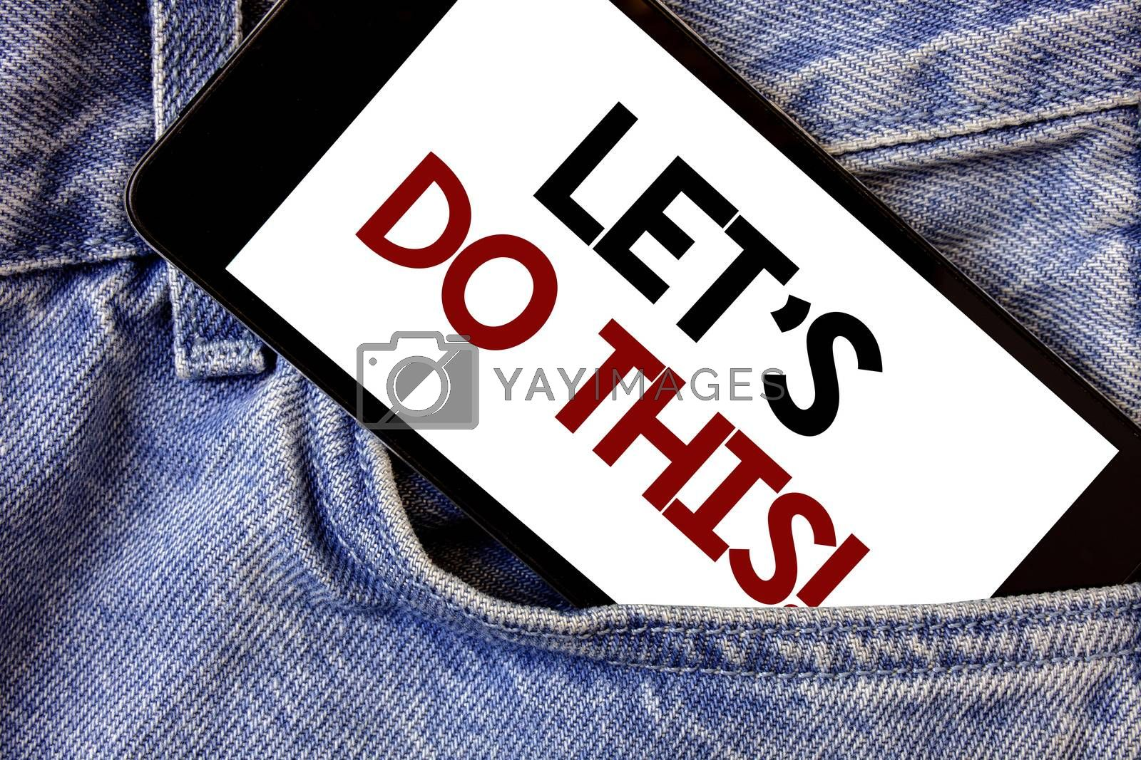 Word writing text Let Us Do This Motivational Call. Business concept for Encourage to start something Inspirational Text two Words written black Phone white Screen front pocket blue jeans