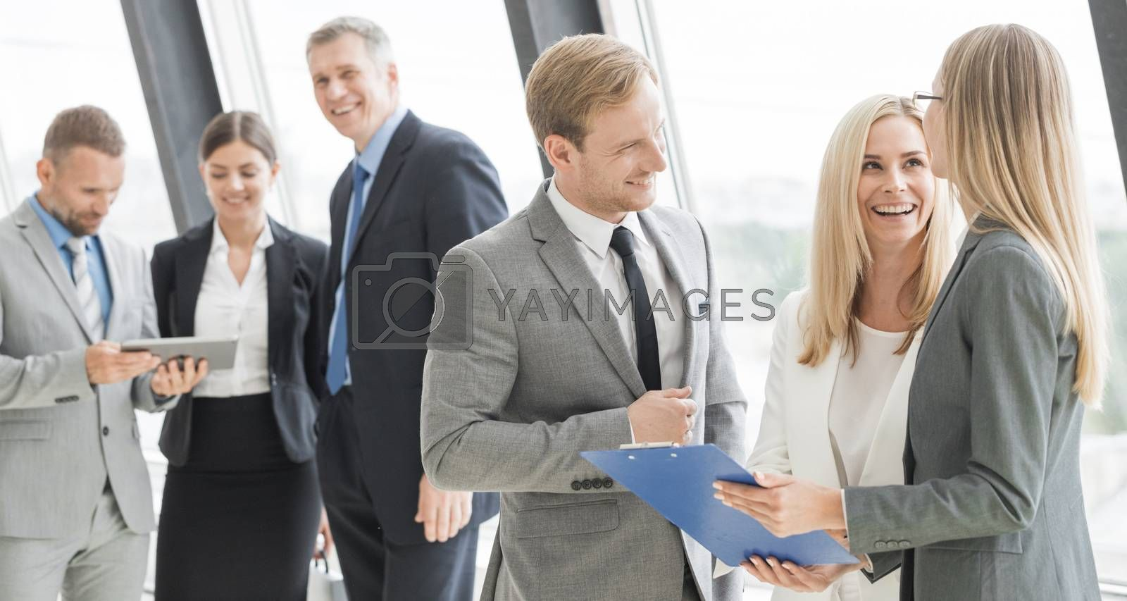 Business people talking at meeting in office near window