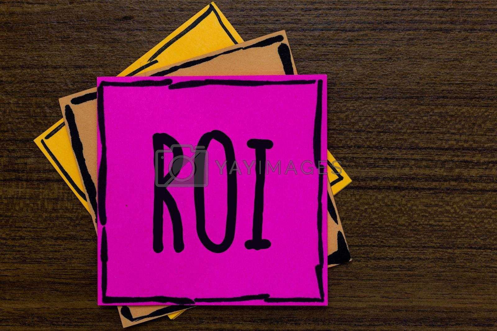 Writing note showing Roi. Business photo showcasing Return on investment performance measure gains business growth Three art small paper two yellow one pink wood brown lite grey shadow