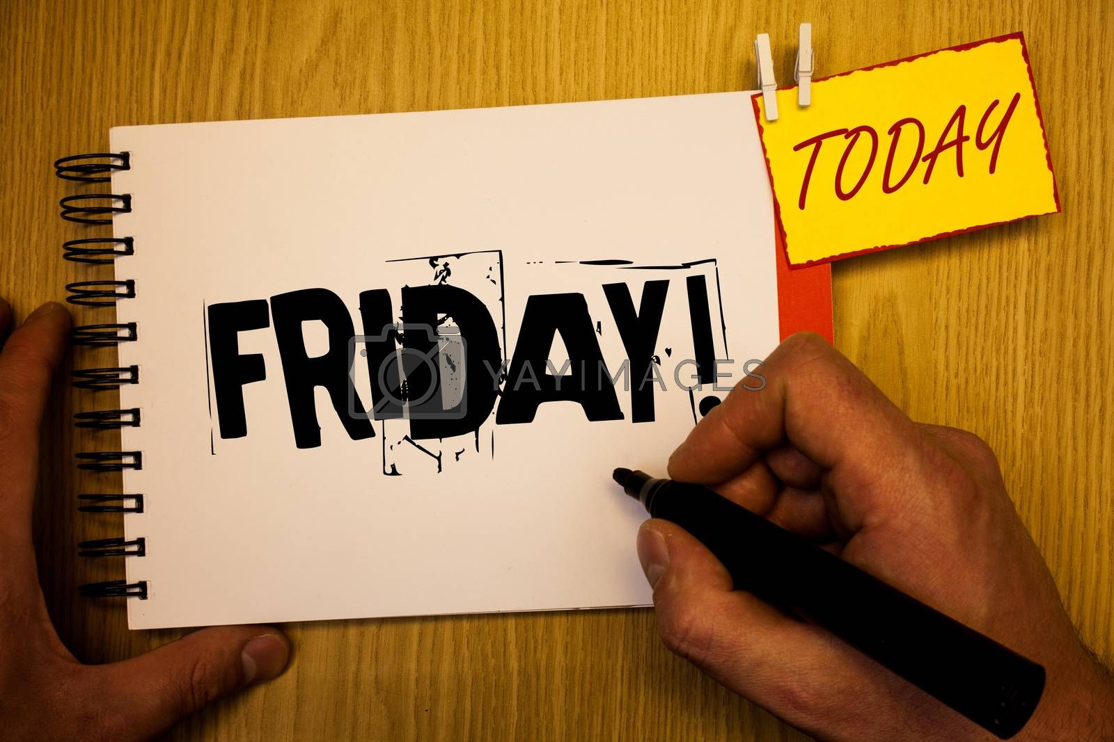 Handwriting text writing Friday Motivational Call. Concept meaning Last day of working week Start weekend Relax time Man hold holding black marker notebook clothespin today wooden table