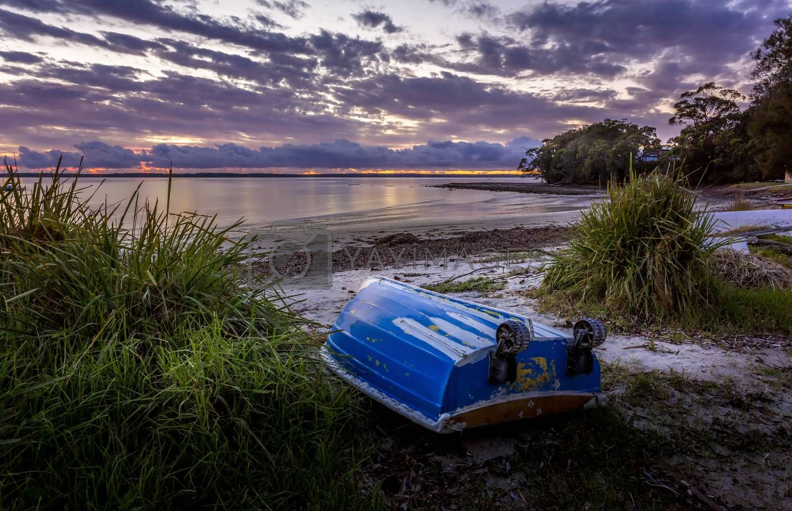"""Little blue rowboat, sometimes called """"tinnies"""" in Australia sits upturned on a beach at dawn with the sky aglow with the first colours of morning"""